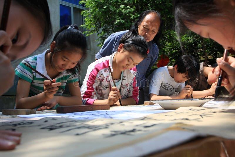 Allievi cinesi del banco primario nell'apprendimento del callig immagine stock