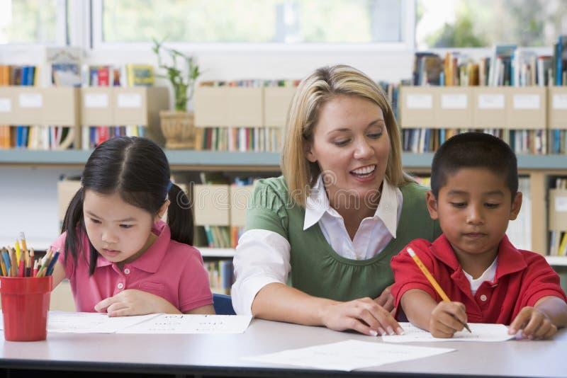 Allievi d'aiuto dell'insegnante con le abilità di scrittura immagini stock