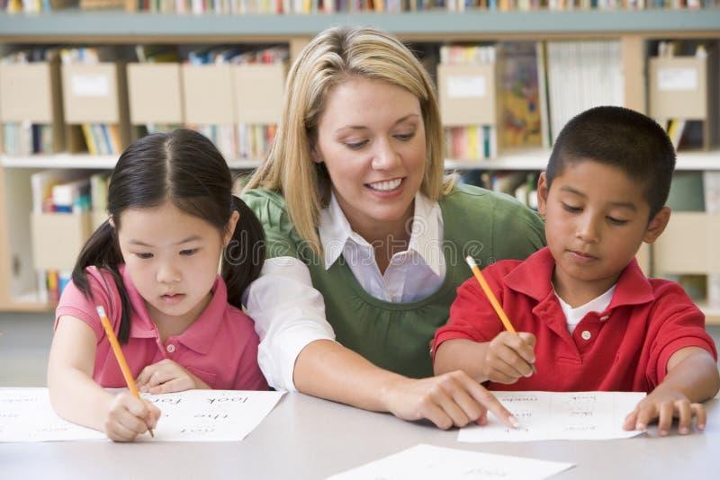 Allievi d'aiuto dell'insegnante con le abilità di scrittura immagini stock libere da diritti