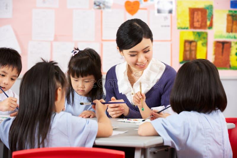 Allievi d'aiuto dell'insegnante durante il codice categoria di arte fotografie stock libere da diritti