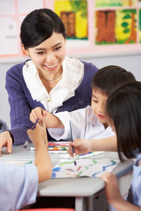 Allievi d'aiuto dell'insegnante durante il codice categoria di arte fotografie stock