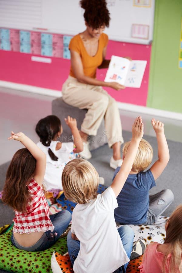 Allievi elementari che sollevano le mani per rispondere alla domanda come aula di Reads Story In dell'insegnante femminile immagini stock libere da diritti
