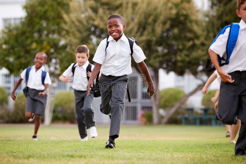 Allievi emozionanti della scuola elementare che indossano funzionamento uniforme attraverso il campo al tempo della rottura immagini stock