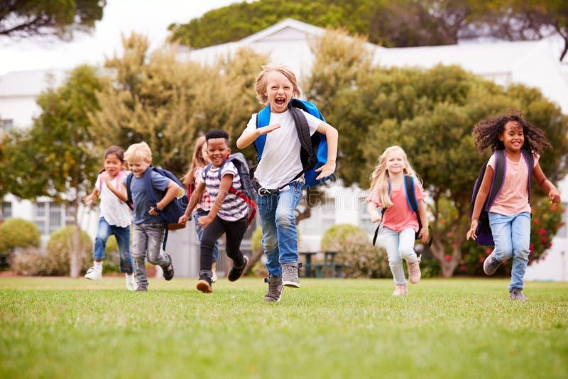 Allievi emozionanti della scuola elementare che si dirigono attraverso il campo al tempo della rottura immagine stock