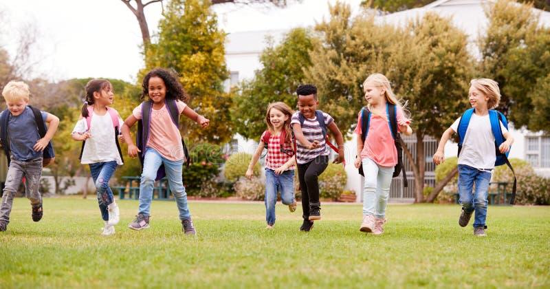 Allievi emozionanti della scuola elementare che si dirigono attraverso il campo al tempo della rottura fotografia stock libera da diritti