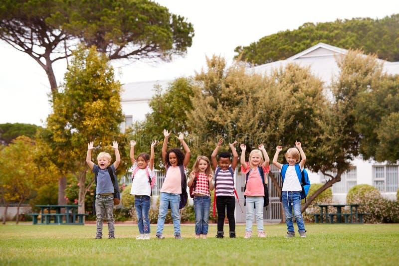 Allievi emozionanti della scuola elementare sul campo da gioco a tempo della rottura immagine stock