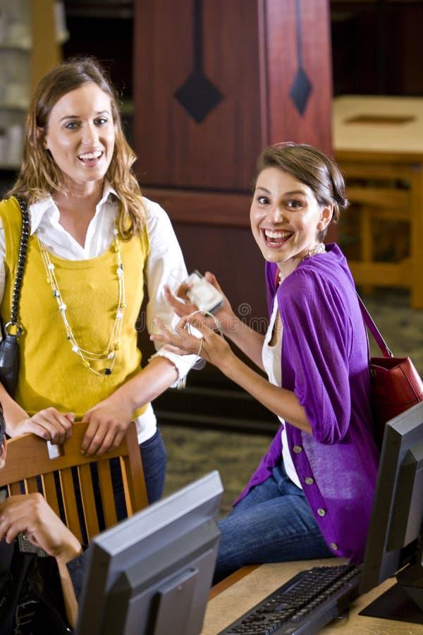 Allievi femminili che appendono fuori dai calcolatori delle biblioteche immagine stock libera da diritti