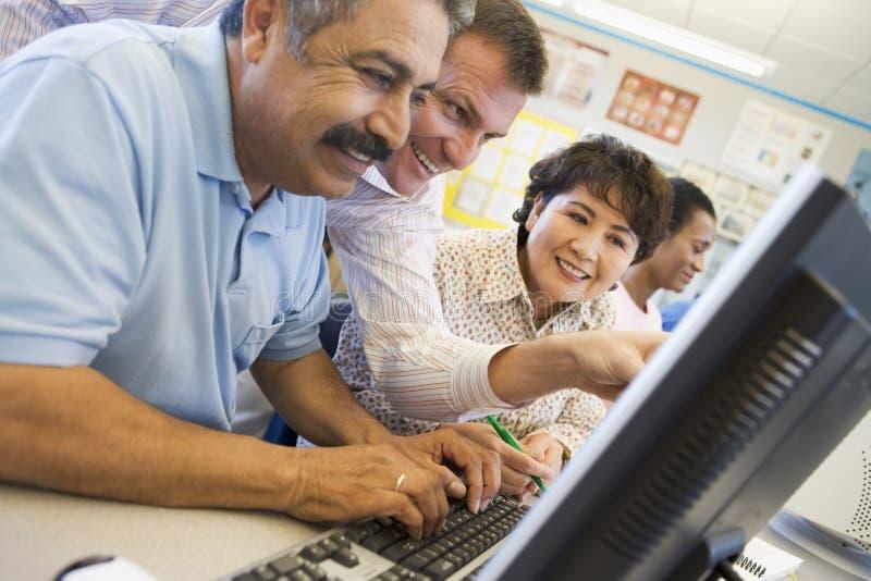 Allievi maturi che imparano le abilità del calcolatore immagini stock libere da diritti