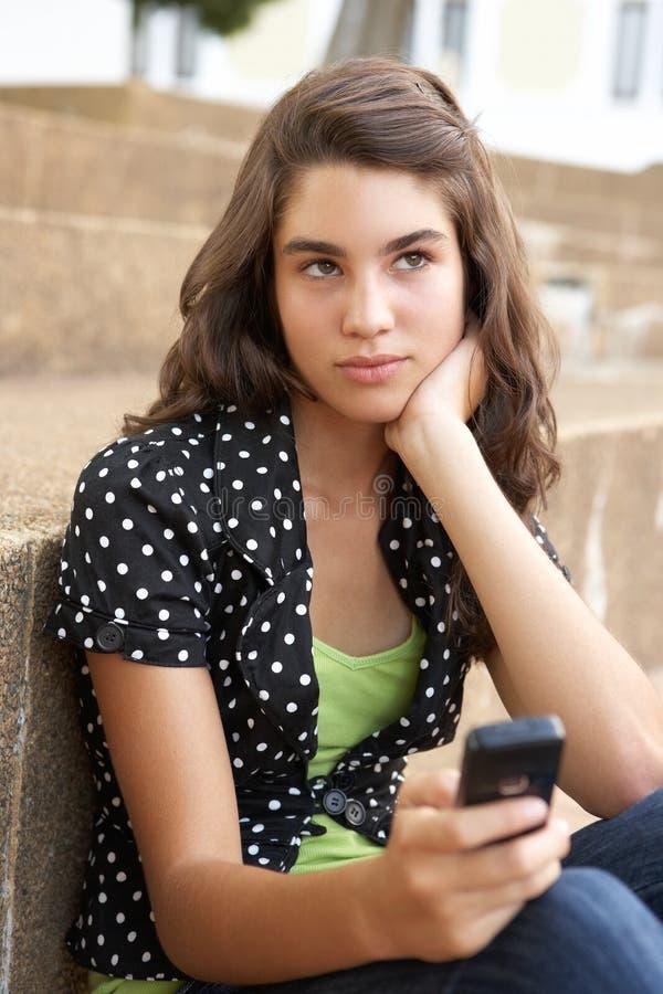 Allievo adolescente infelice che si siede all'esterno immagini stock libere da diritti