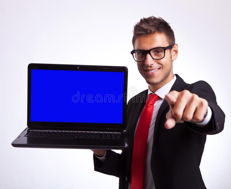 Allievo che indica voi per vincere un nuovo computer portatile fotografia stock