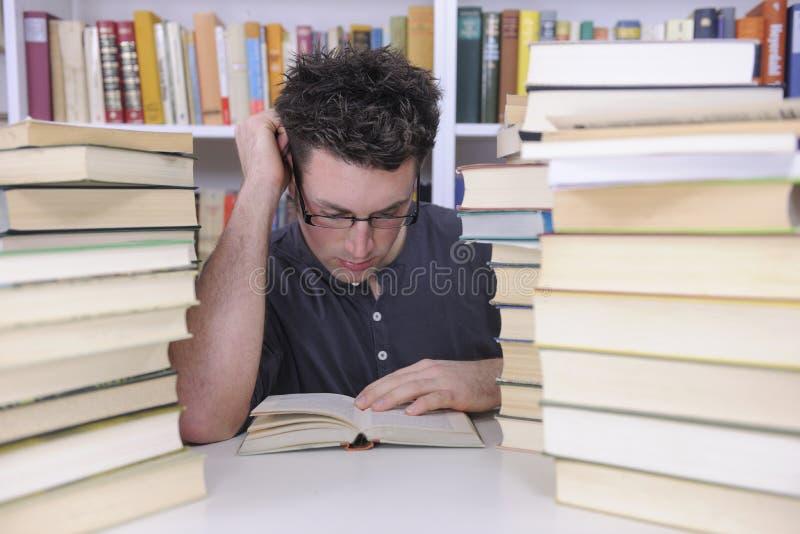 Allievo che ricerca con i libri in una libreria fotografia stock libera da diritti