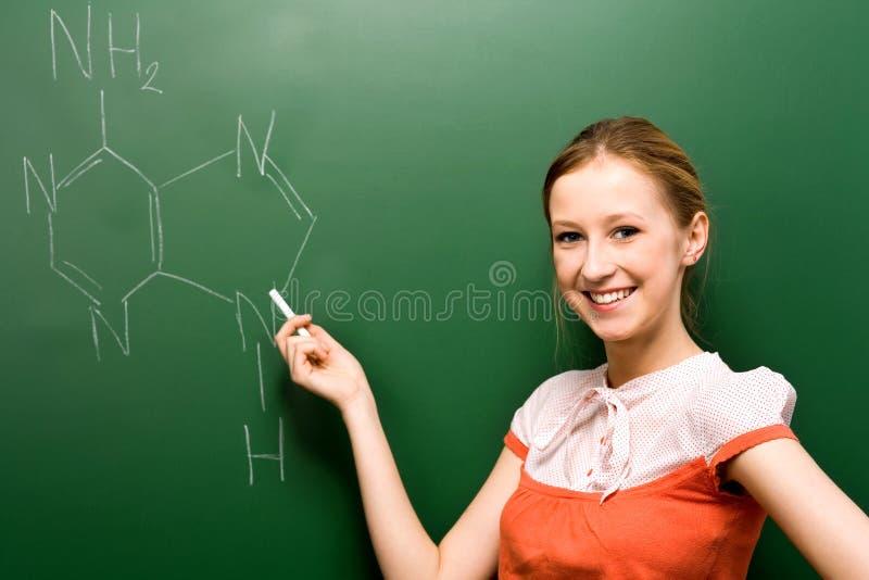 Allievo che scrive i simboli chimici fotografia stock libera da diritti
