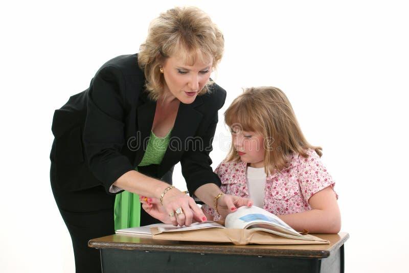 Allievo d'aiuto uno dell'insegnante su uno fotografie stock libere da diritti