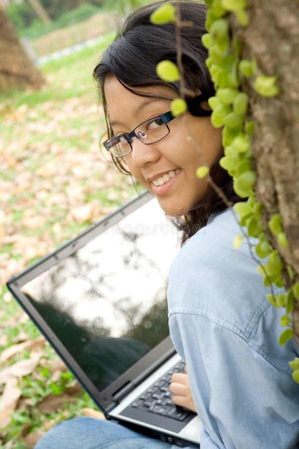 Allievo dell'adolescente che lavora al computer portatile fotografia stock libera da diritti