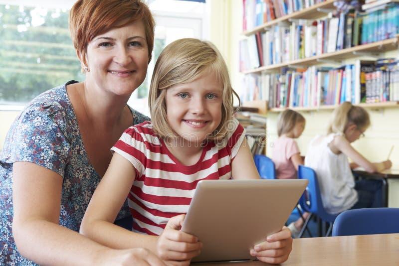 Allievo della scuola con il computer di Using Digital Tablet dell'insegnante nella classe fotografie stock libere da diritti