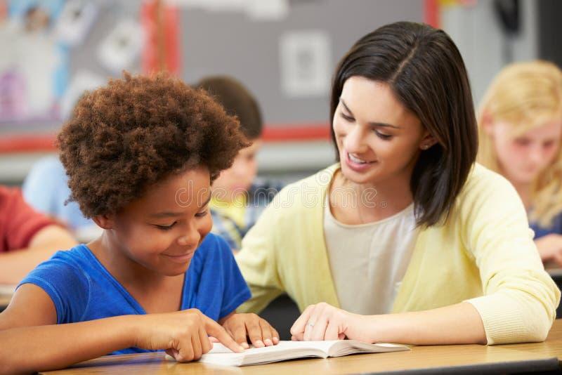 Allievo di Reading With Female dell'insegnante nella classe fotografie stock
