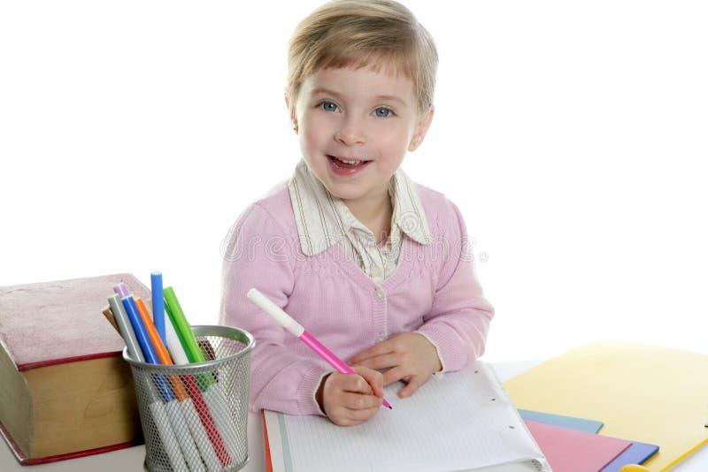 Allievo felice della bambina su scrittura dello scrittorio fotografia stock
