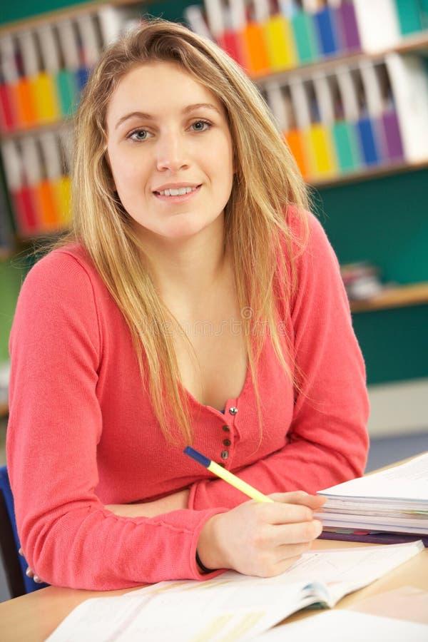 Allievo femminile adolescente nel funzionamento nell'aula immagine stock