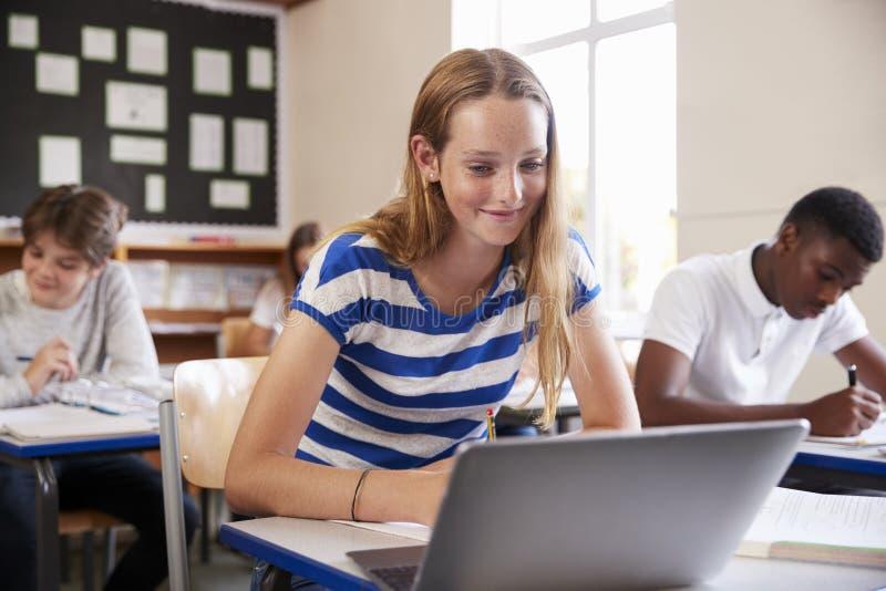 Allievo femminile che si siede allo scrittorio nella stanza di classe facendo uso del computer portatile immagine stock libera da diritti
