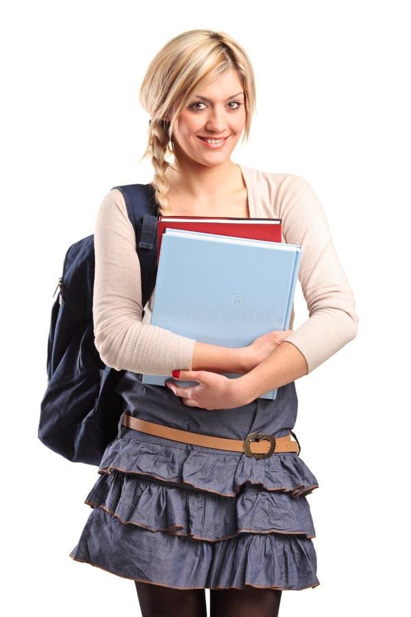 Allievo femminile sorridente con un sacchetto di banco fotografia stock libera da diritti