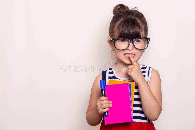 Allievo pronto per il banco La cancelleria dei bambini per scuola Bambino con il taccuino e penna in mani fotografie stock