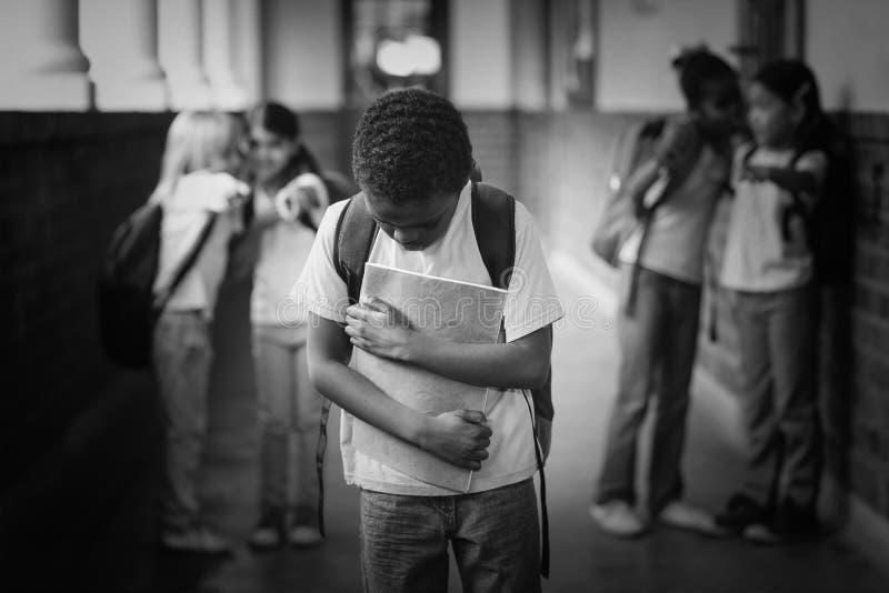 Allievo triste che è oppresso dai compagni di classe al corridoio fotografia stock libera da diritti