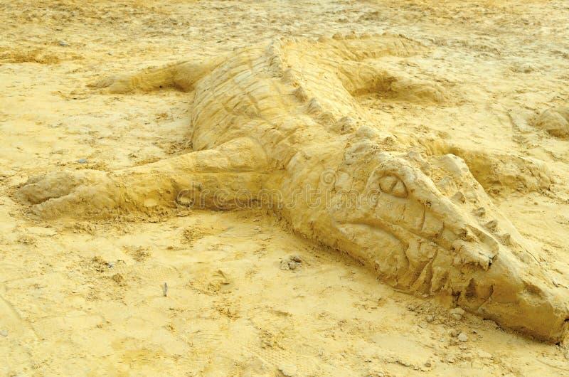 Alligator sculpture on sand at seaside stock images
