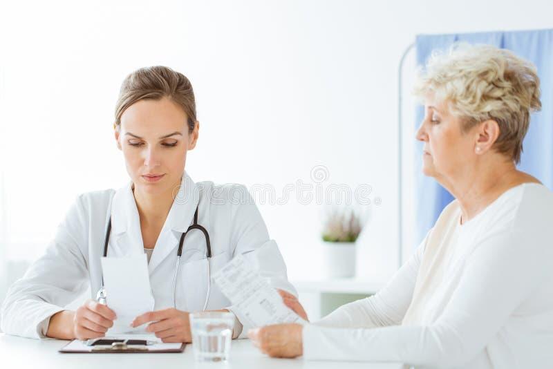 Allmän doktor som konsulterar med patienten royaltyfria bilder