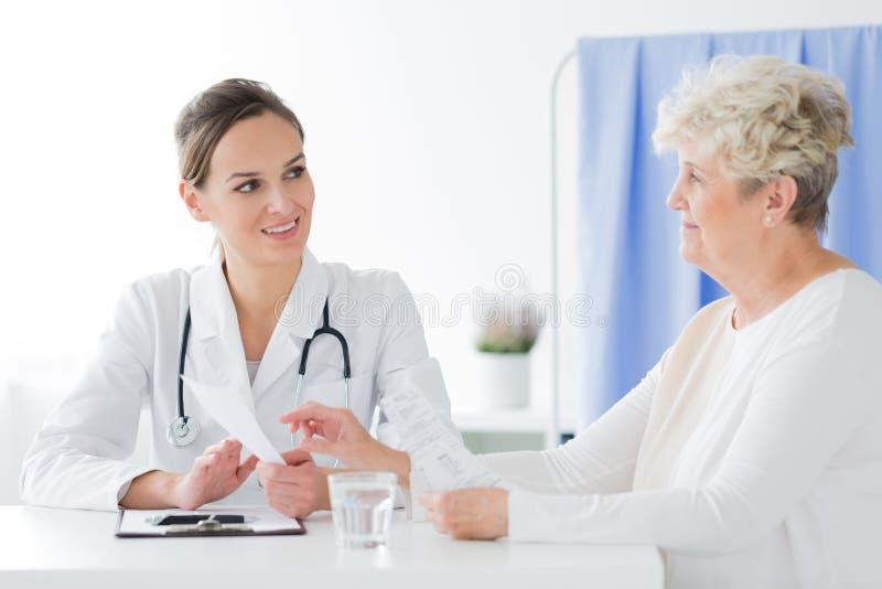 Allmän praktiker som gör medicinsk intervju royaltyfri fotografi