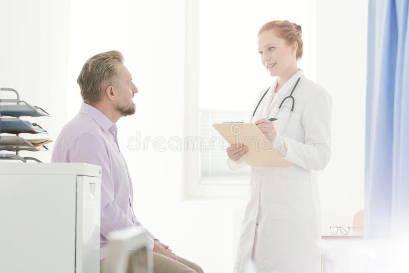 Allmän praktiker som talar till patienten royaltyfri bild
