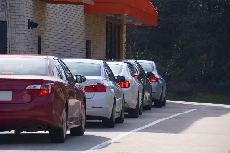 Allmänna drivrutiner genom upphämtningsfönster med bilar som väntar på att få sina produkter eller mat royaltyfria foton