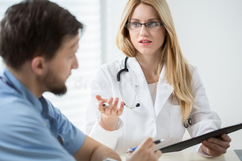 Allmäntjänstgörande läkare som konsulterar med annan doktor royaltyfri fotografi