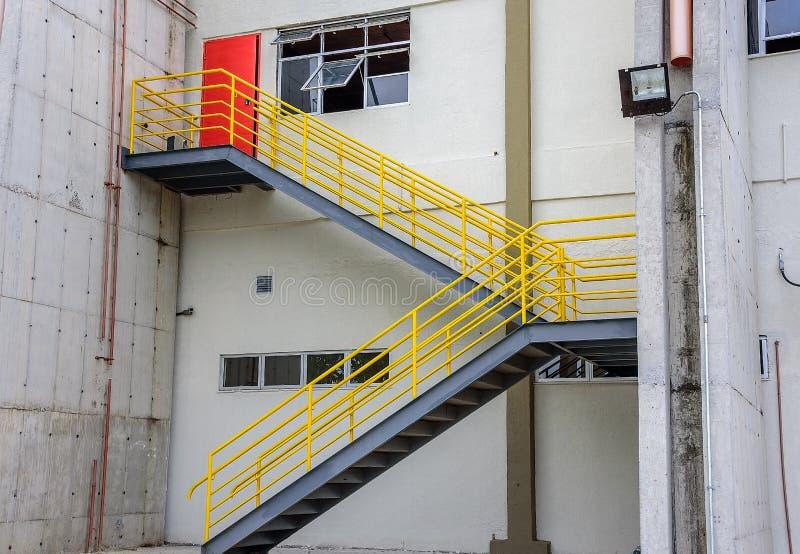 Allo scalo merci nel vecchio aeroporto di Galeao, nella costruzione bianca, nella scala con l'inferriata gialla e nella porta ros fotografia stock
