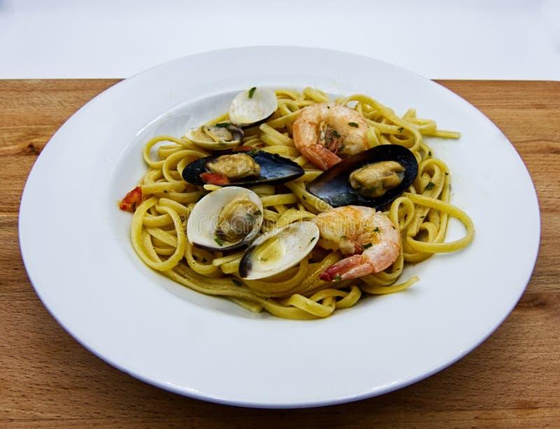Allo scoglio för Linguine, maträtt av italiensk pasta med skaldjur på trätabellen royaltyfria foton