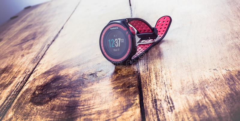 Alloa, Scotland - 17 July 2019: GARMIN FORERUNNER Multisport Watch isolated on wooden background royalty free stock image