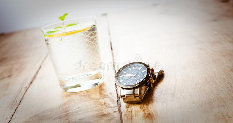 Alloa, Scotland - 17 July 2019 - watch and glass of water isolated on a wooden table. Accurist man watch royalty free stock photo