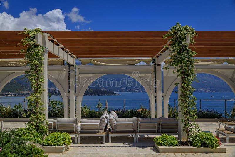 Allocation des places extérieure dans un restaurant dans Budva avec vue sur la vieille ville et la Mer Adriatique dans Monténégro photos libres de droits