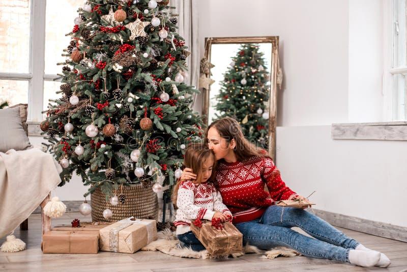 Allocation des places heureuse de mère et de fille près de sapin photos libres de droits