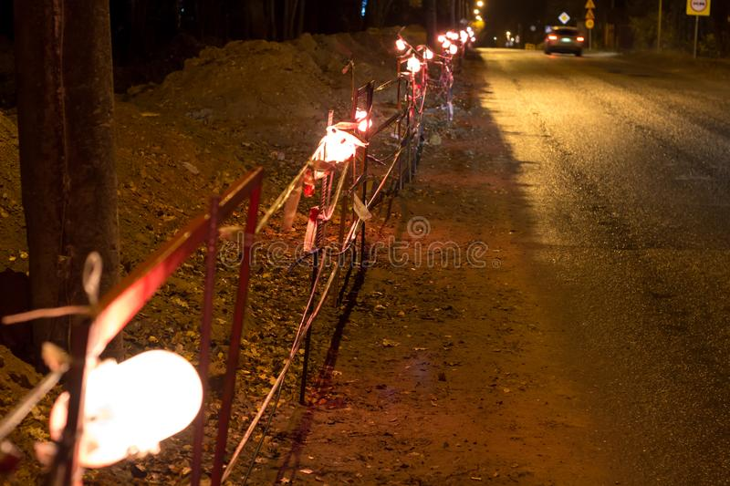 Allocation of the work site in the evening by lamps. Repair work along the road. Allocation of the work site in the evening by lamps royalty free stock images