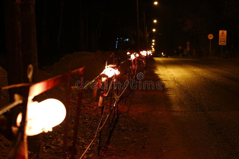 Allocation of the work site in the evening by lamps. Repair work along the road. Allocation of the work site in the evening by lamps royalty free stock photos