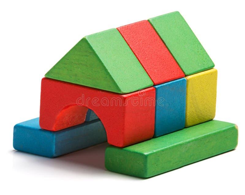 Alloggi i blocchetti del giocattolo ha isolato il fondo bianco, casa di legno immagine stock