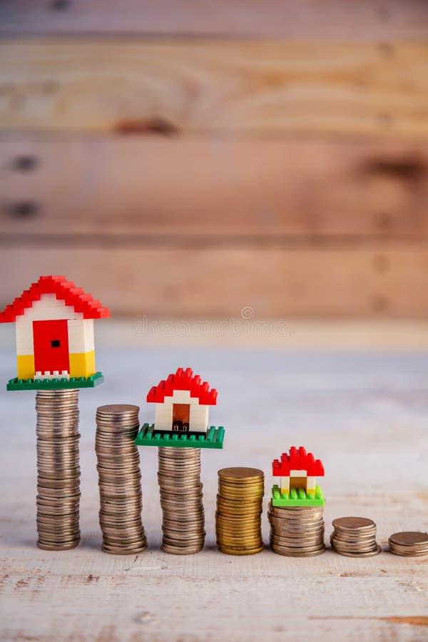 Alloggi i modelli con le monete impilate al patrimonio aziendale di legno c della tavola fotografie stock libere da diritti