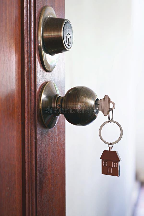 Alloggi la chiave con l'anello portachiavi domestico in buco della serratura, concetto della proprietà fotografie stock