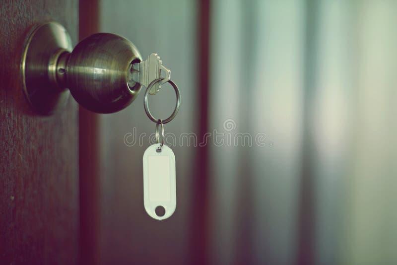 Alloggi la chiave con l'anello portachiavi domestico in buco della serratura, il concetto della proprietà, Empty tag fotografia stock