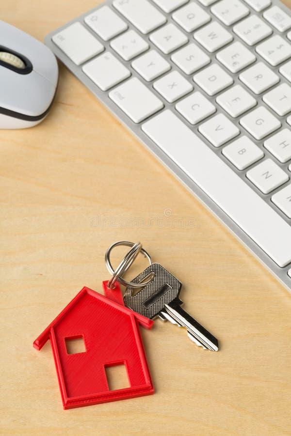 Alloggi la chiave della porta con il pendente rosso ed il tasto del computer della catena chiave della casa fotografia stock libera da diritti