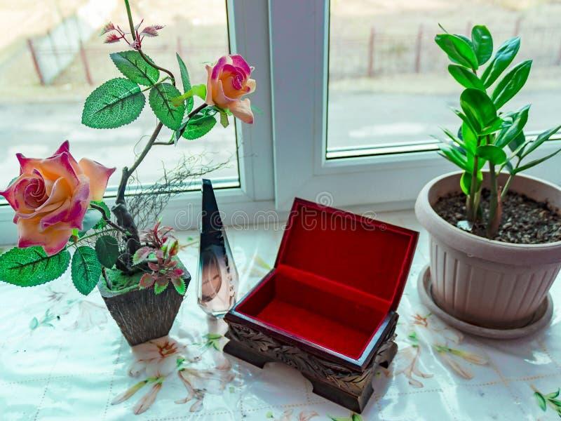 Alloggi le rose artificiali del fiore e un bello cofanetto sul davanzale fotografia stock