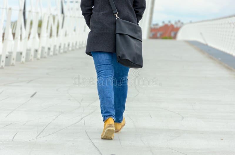 Allontanarsi d'uso dei jeans e della borsa della donna fotografia stock