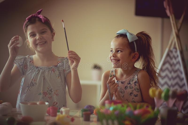 Always allow them to be free to create. Little girls coloring Easter egg stock photography