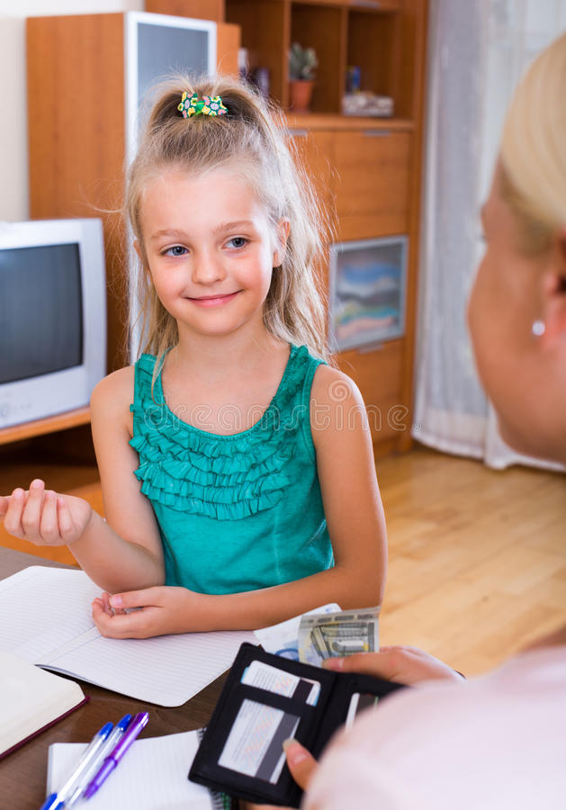 Allowance of pocket money. Cute smiling little girl and mother with purse royalty free stock image