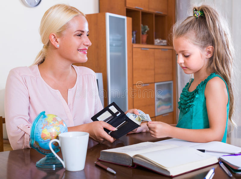 Allowance of pocket money. Little girl and smiling mother with purse royalty free stock photography
